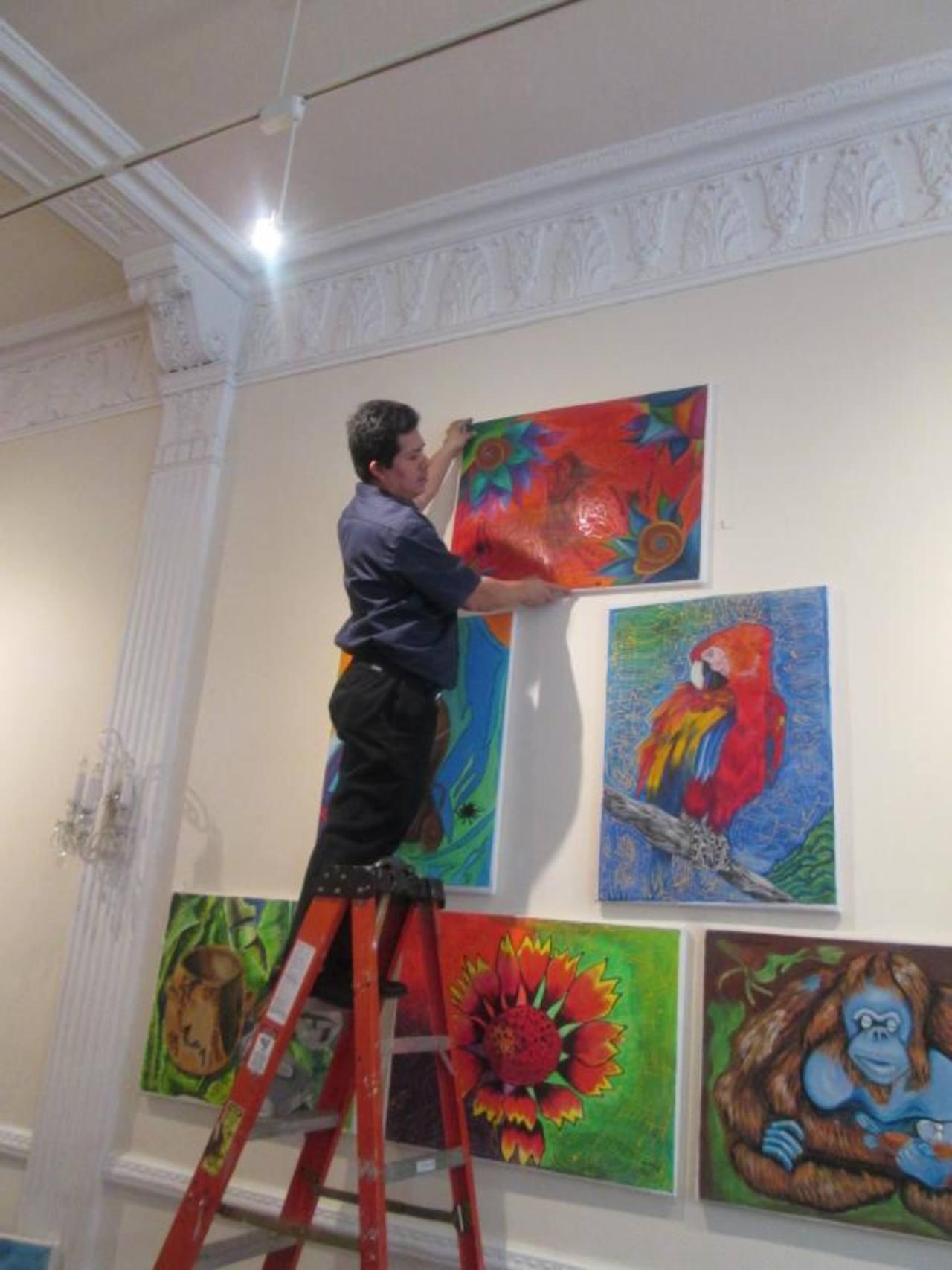 Luis Machuca, colaborador de la Misión salvadoreña ante la ONU, coloca las pinturas de los estudiantes del centro escolar Distrito Italia, de cara a la exposición en Nueva York. Fotos EDH /