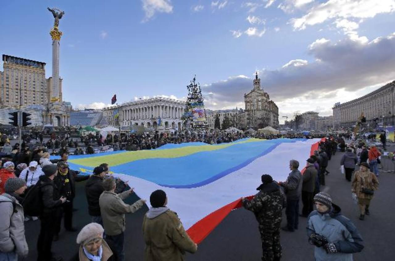 Varias personas sujetan una bandera ucraniana unida a una de Crimea durante una protesta convocada en Kiev. foto edh / efe