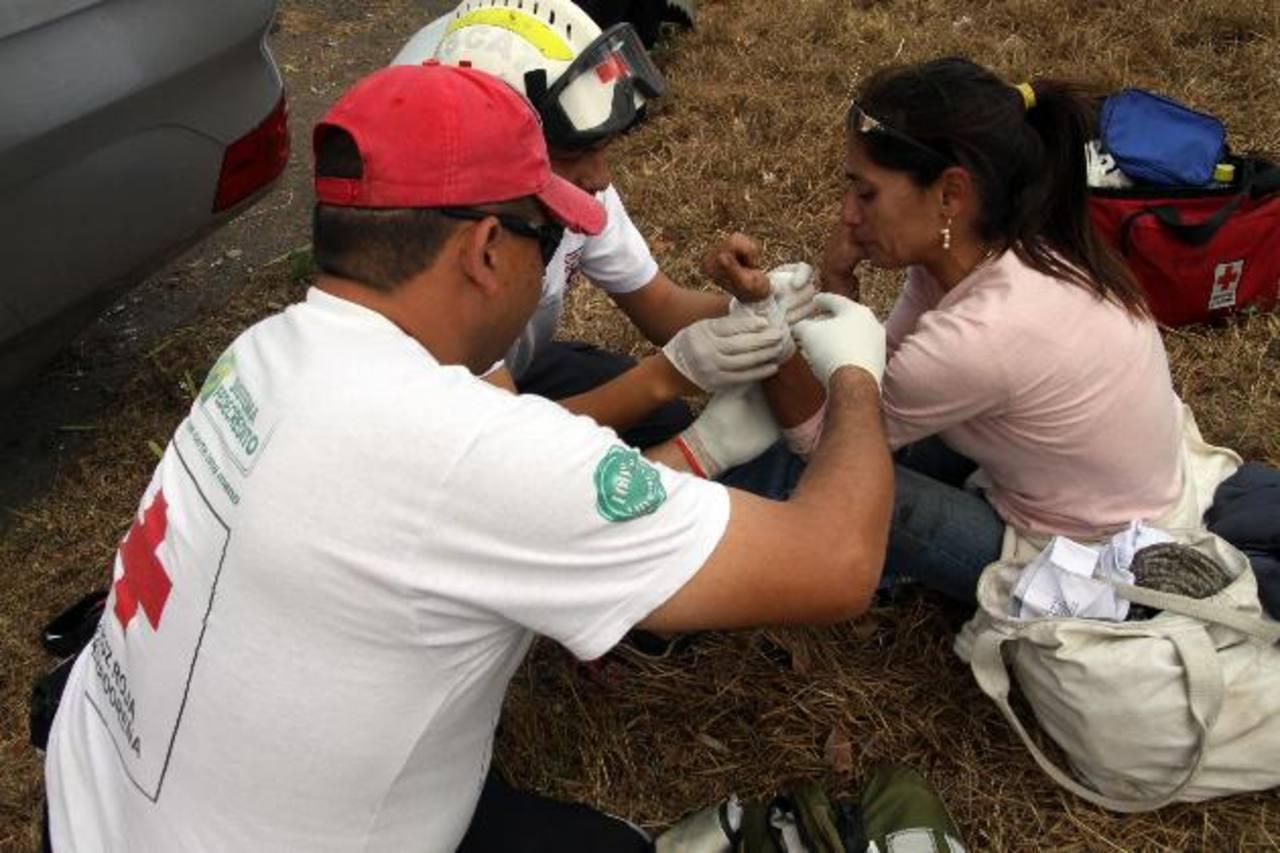 Rescatistas de la Cruz Roja atienden a una señora que sufrió golpes leves tras el accidente. Foto EDH / César AvilésLos hechos se originaron luego que la víctima no pagara la cuenta en un bar tecleño. Foto EDH / Archivo