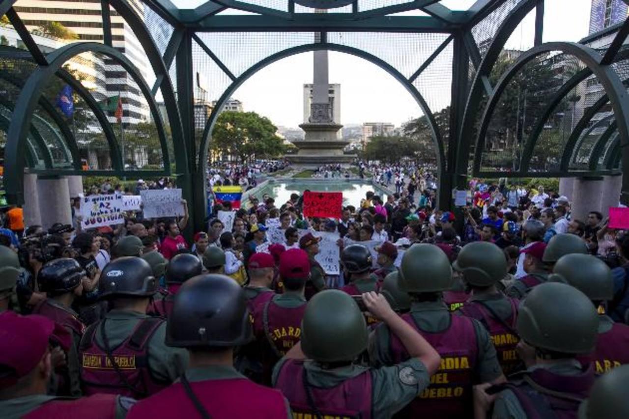 Agentes de la Guardia del Pueblo vigilan a un grupo de personas opositoras al gobierno de Maduro durante una manifestación pacífica que se realizó en la Plaza Altamira en Caracas, Venezuela. foto edh / EFE