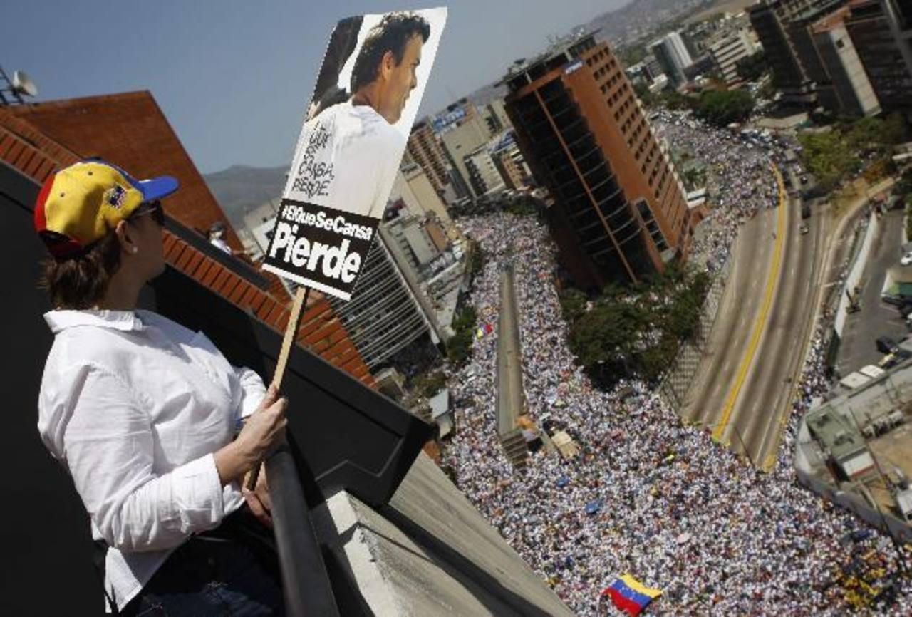 Una partidaria de la oposición observa la multitudinaria protesta contra Maduro ayer en Caracas, mientras sostiene una pancarta con la fotografía de Leopoldo López. Foto edh/Reuters