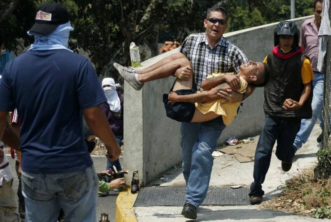 Un hombre lleva a un manifestante que resultó herido durante una protesta en San Cristóbal (Táchira) contra el gobierno de Nicolás Maduro. foto edh / Reuters