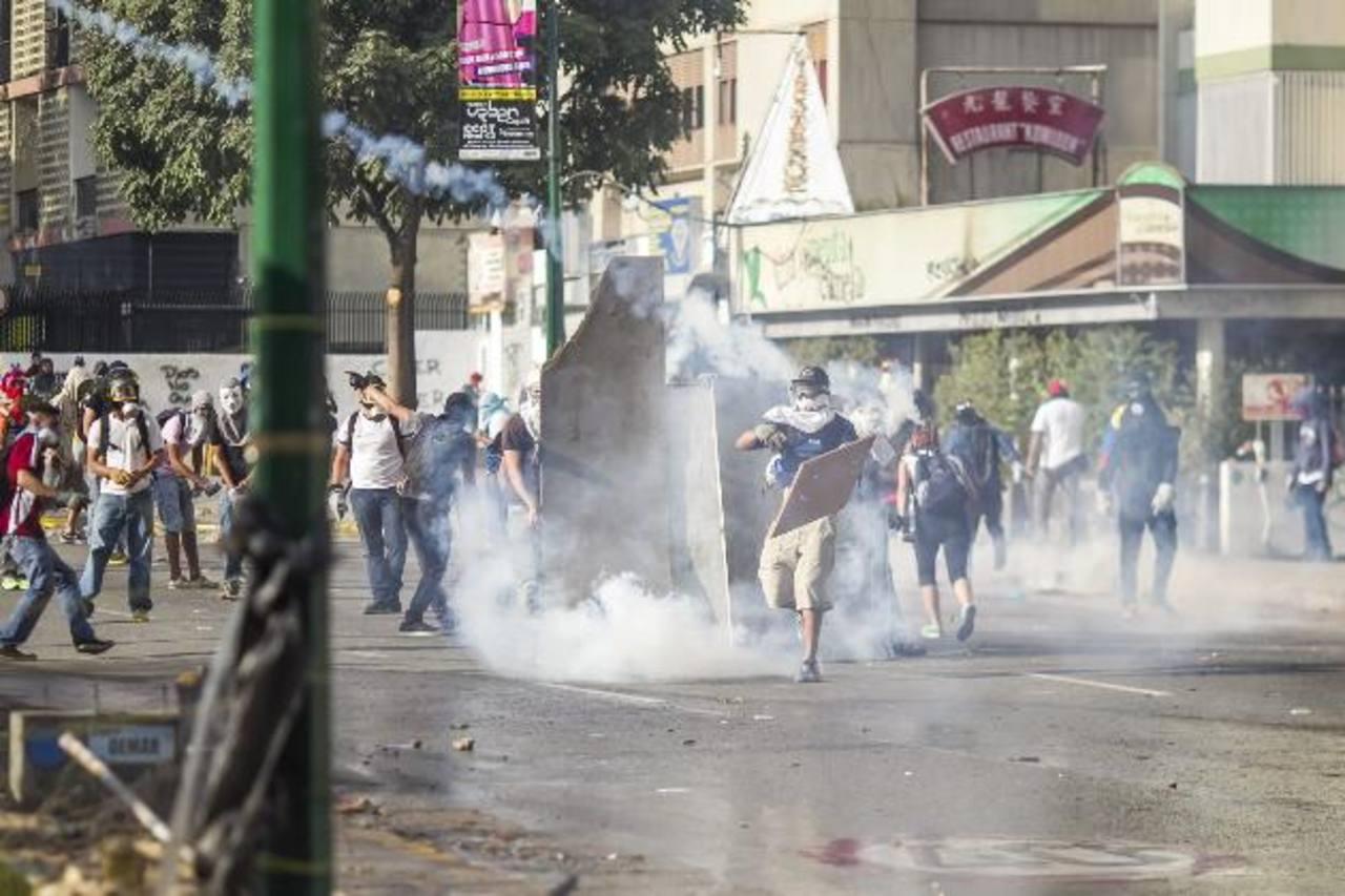 Un grupo de jóvenes protesta contra el régimen venezolano en el sector Chuao, en la capital venezolana. foto edh / EFE
