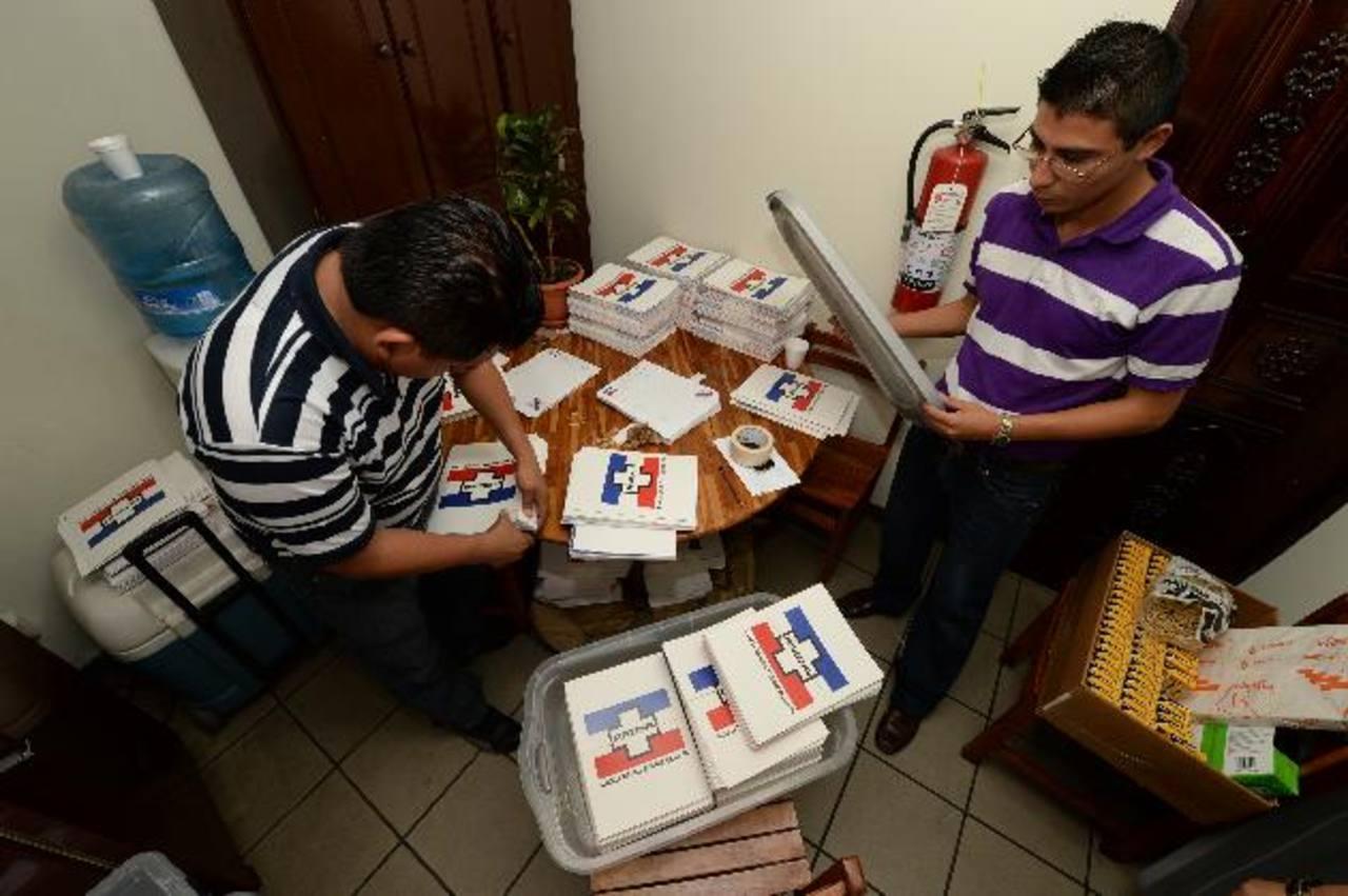 Voluntarios preparan las carpetas para consultar temas del congreso a las bases y estructuras del partido. Foto EDH / Jorge reyes