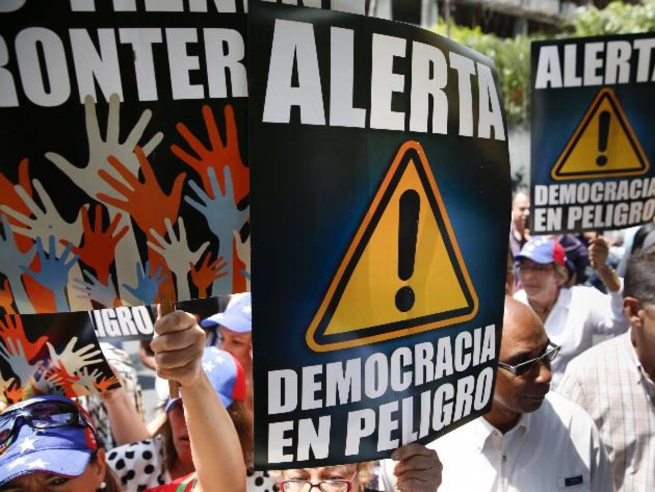 Manifestantes opositores sostienen pancartas ayer durante una protesta contra el Gobierno de Nicolás Maduro, frente a Embajada de Portugal en Caracas. Hoy se cumple un mes de incesantes marchas en ese país. foto edh/Reuters