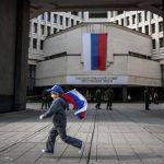 Niño corre con la bandera rusa en la península de Crimea. Foto AP