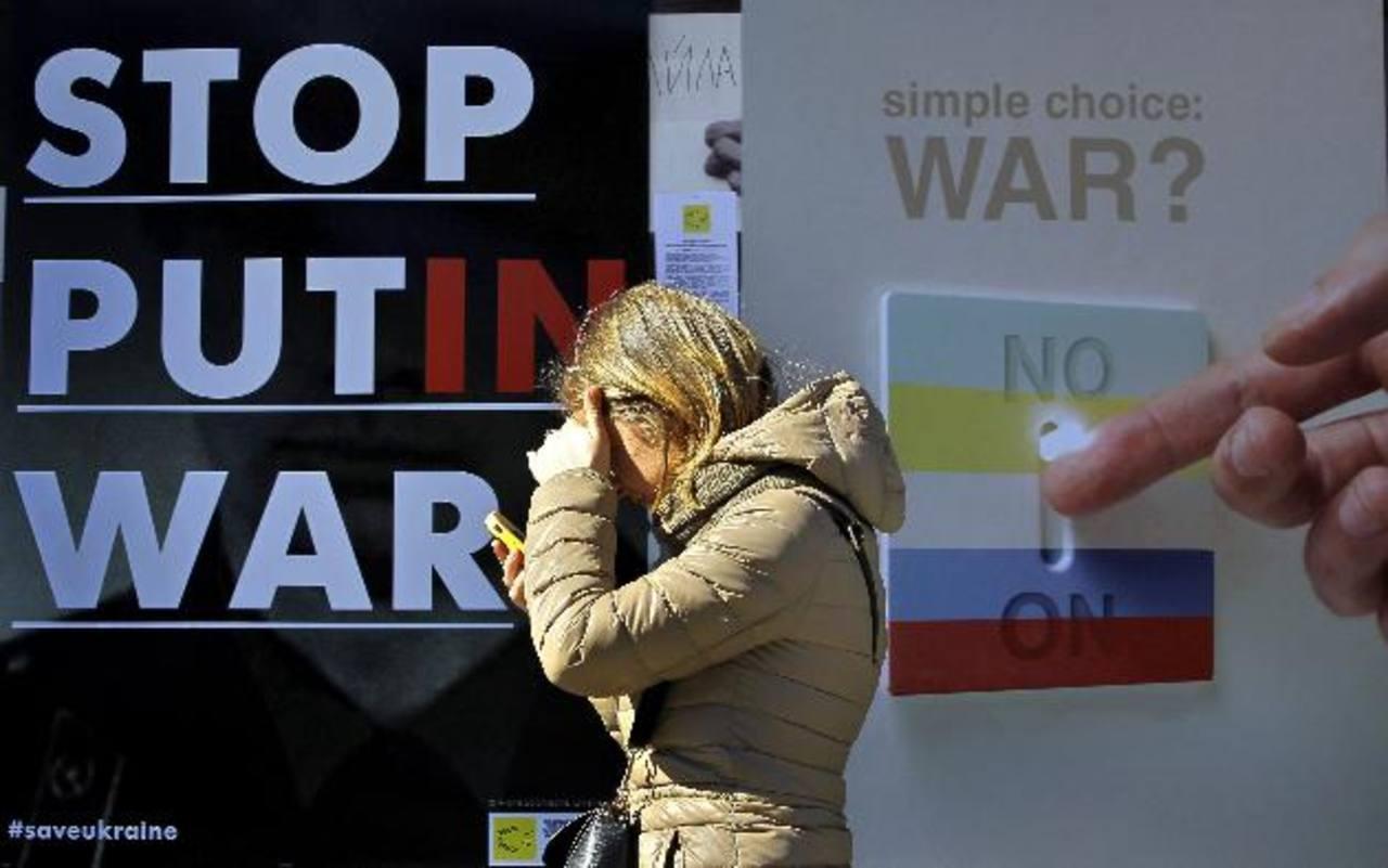 Una mujer pasa ayer frente a una exposición de estudiantes sobre el conflicto de Rusia y Crimea, en Kiev. foto EDH /EFE
