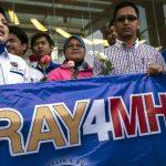 Familiares de pasajeros que viajaban a bordo del avión de Malasia Airlines desaparecido sostienen una pancarta y ofrecen flores un hotel de Putrajaya (Malasia). Foto/ EFE
