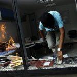Un opositor al Gobierno de Nicolás Maduro en Venezuela salta por una ventana tras incendiar una oficina pública en Caracas. Foto Reuters