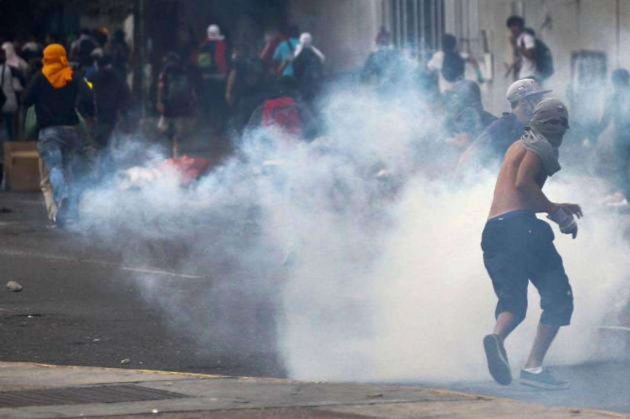 Manifestantes son repelidos por bombas de gas de la Policía Bolivariana, ayer, en una protesta en Caracas. foto edh / reuters