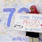 Una mujer muestra un mural con mensajes de apoyo a los pasajeros del vuelo MH370 de Malaysian Airlines desaparecido hace una semana. foto EDH / efe