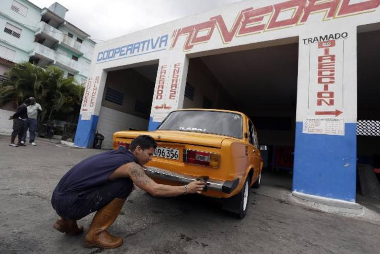 """Un hombre aplica silicon a un vehículo Lada, de fabricación soviética, en el taller cooperativo """"Novedades"""", en La Habana, Cuba. FOTO DE EXPANSIÓN/ REUTERS"""