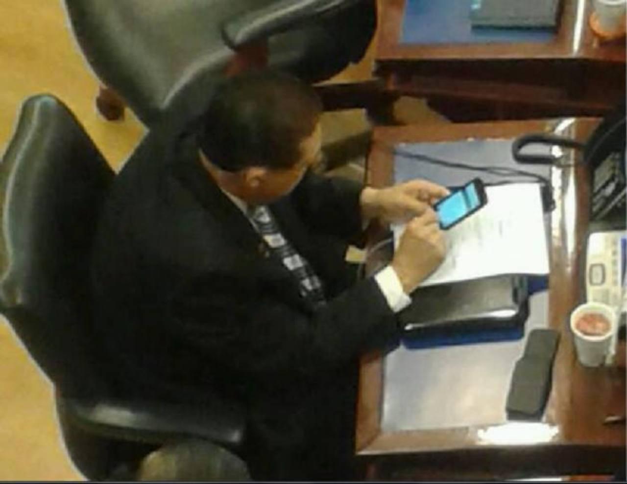 Rodrígo Samayoa en su curul revisando su celular y tomando jugo de tomate. FOTO EDH tomado de @ojoatento