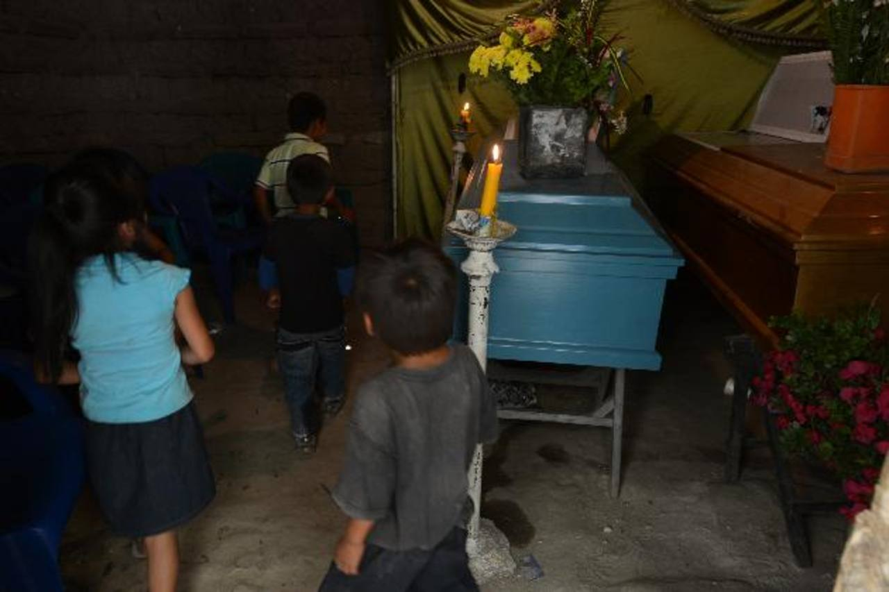Cuatro de los niños huérfanos pasan frente a los ataúdes de su padre y de su hermano mayor, asesinados el lunes en Monte San Juan. Foto EDH / Mauricio Cáceres