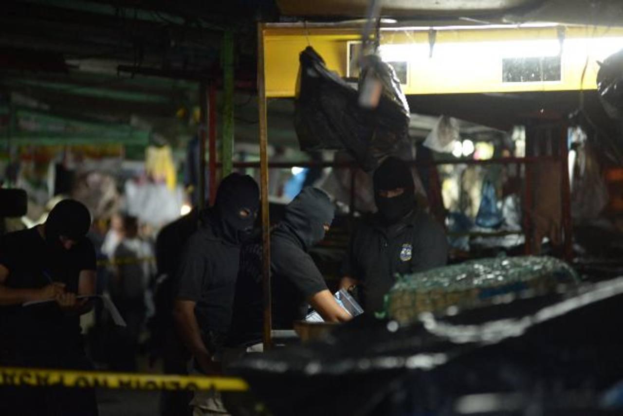 Investigadores inspeccionan el sitio del ataque en mercado Central. Foto EDH/ SALOMÓN VÁSQUEZ