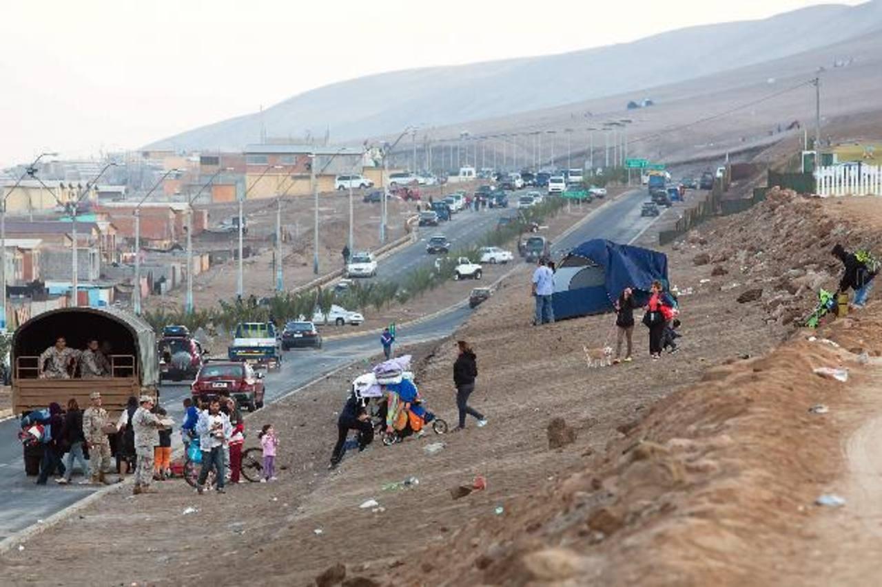 Unas personas bajan por un cerro de regreso a su casa, luego de ser levantada la alerta de tsunami en Arica (Chile). foto edh /EFE