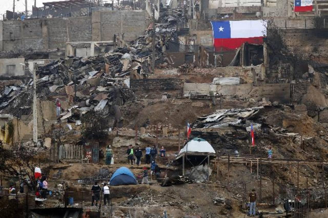 Voluntarios y residentes limpian escombros en una zona arrasada por el fuego en el cerro la Cruz, en Valparaíso.foto edh/EFE