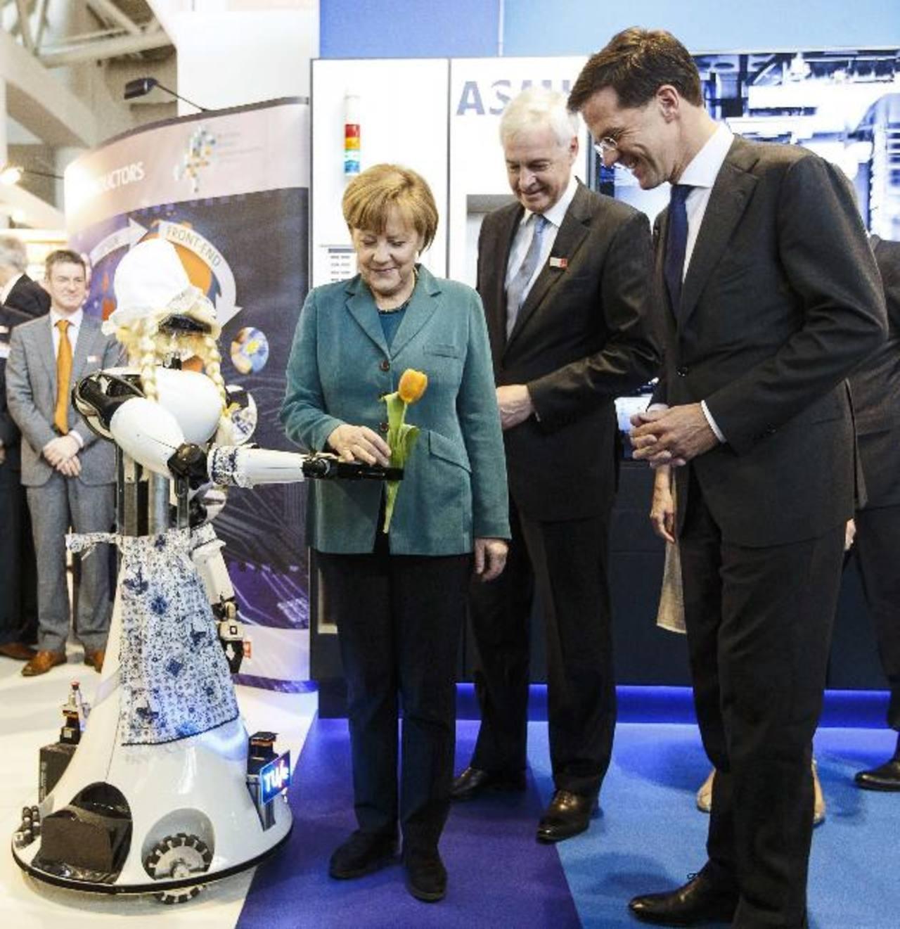 El stand de ASML un robot con peluca rubia y traje típico de Delft le entregó un tulipán a Angela Merkel. foto edh