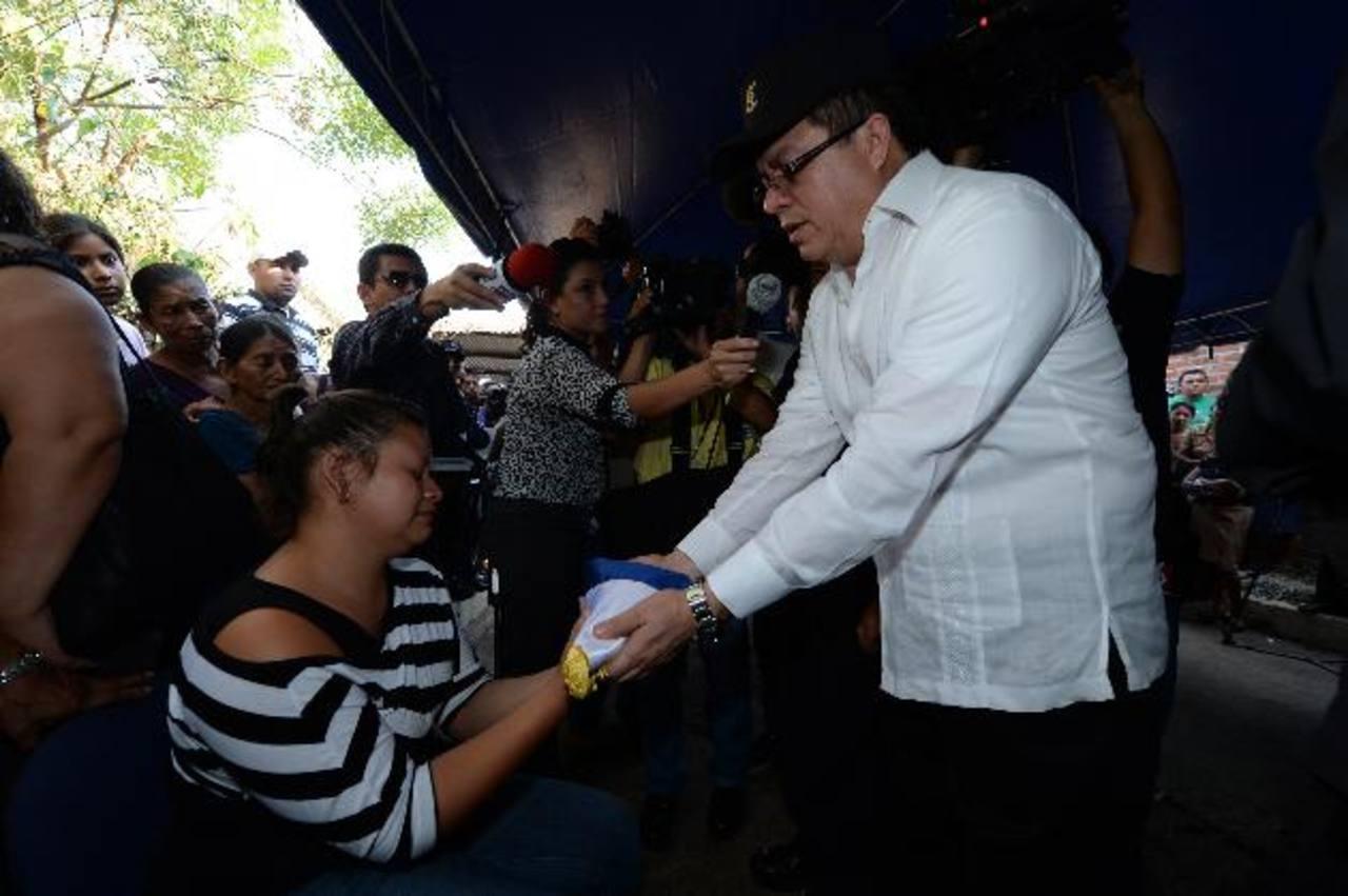 Rigoberto Pleités, director de la PNC, entrega el Pabellón Nacional a la esposa del agente asesinado. Fotos EDH / Jorge Reyes