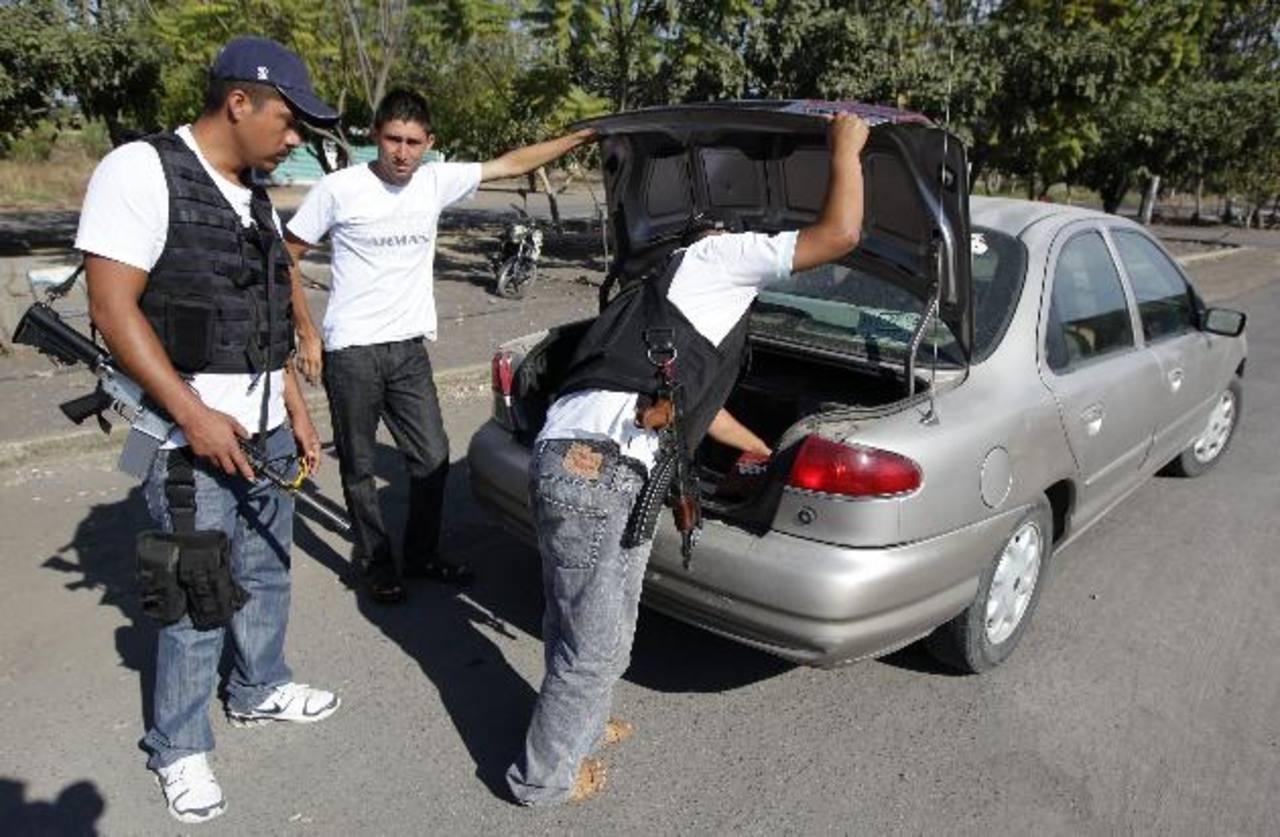 Imagen del domingo 23 de febrero de un grupo de autodefensas inspeccionando los autos en la comunidad de Antúnez, en el estado de Michoacán. foto edh / efe