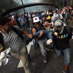 Un manifestante es evacuado herido en una pierna durante una protesta antigubernamental en Caracas, Venezuela. Foto AP