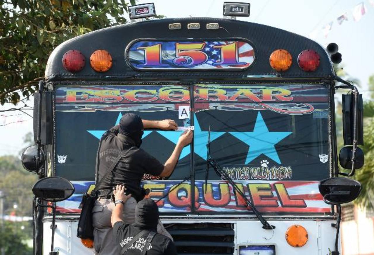 Investigadores de la Policía inspeccionan el bus de la Ruta 151, cuyo cobrador fue asesinado ayer por pandilleros. El crimen se registró cuando el autobús circulaba frente a la alcaldía de San José Villanueva, La Libertad. Foto EDH / Claudia Castillo