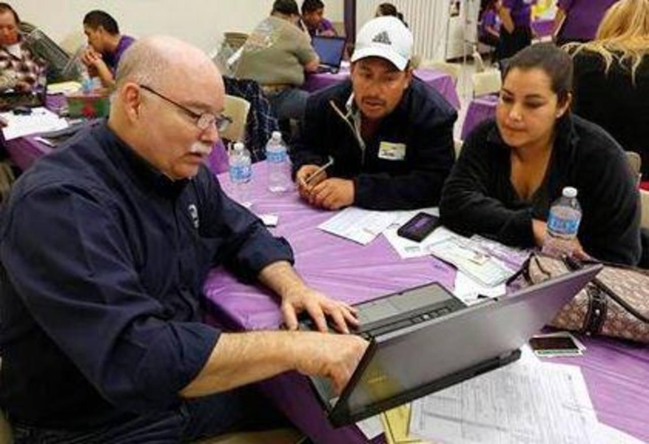 José Gómez y su esposa, Laura, reciben ayuda del agente de seguros Michael Wilson (izquierda) para inscribirse a un plan de seguro médico, en California. Foto/ AP