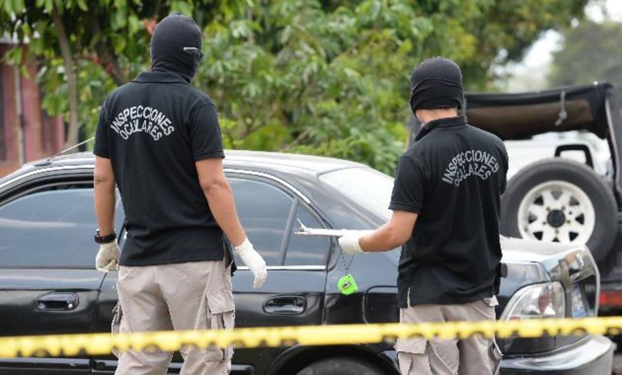 Investigadores de la Policía inspeccionan el auto del militar muerto ayer en Hacienda San José. Foto EDH / Claudia Castillo