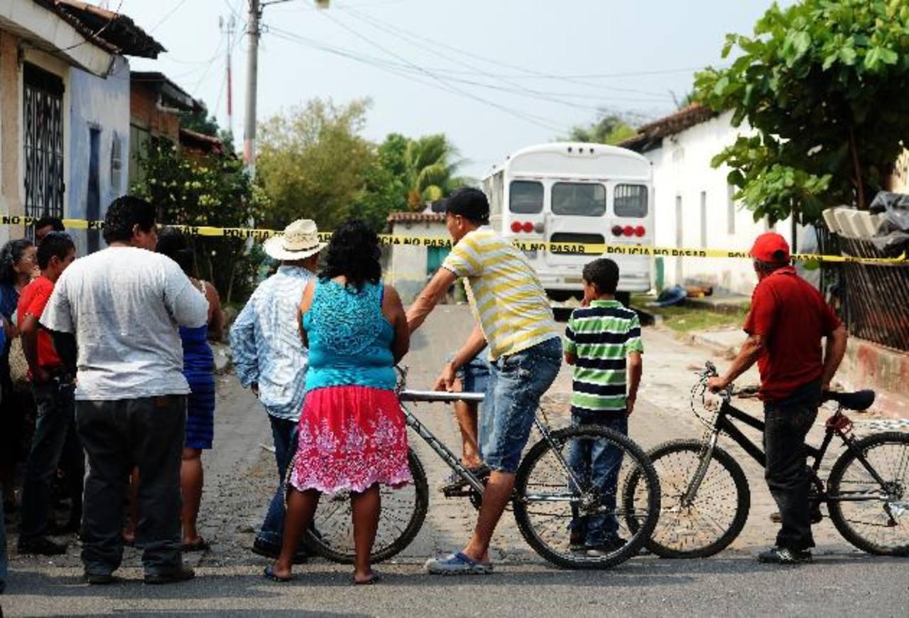 Personas observan el cadáver de un joven que ayer, al mediodía, fue asesinado en el centro de Quezaltepeque. Foto EDH/ MARLON HERNÁNDEZ
