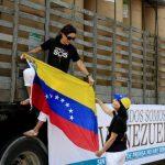 Dos mujeres colocan un a bandera de Venezuela en uno de los dos camiones cargados con 75 rollos de papel periódico desde Colombia. foto edh / EFE
