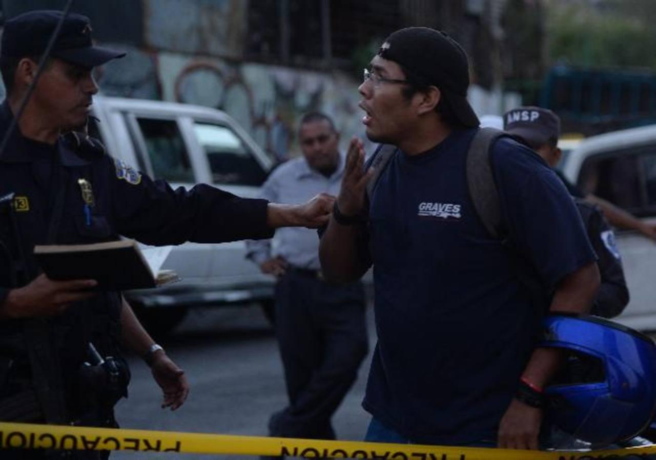 Un agente informa a una persona la muerte de su pariente en Mejicanos. Foto EDH / M. Hernández.