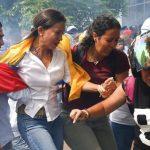 María Corina Machado huye del gas lacrimógeno luego de intentar entrar en la asamblea. Foto Reuters