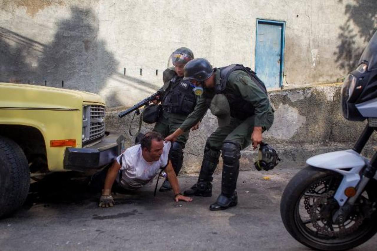 Miembros de la Guardia Nacional Bolivariana detienen a un hombre durante una manifestación de opositores al régimen. Foto edh / efe