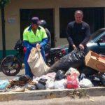 El alcalde (derecha) Carlos Figueroa al momento de recoger la basura.
