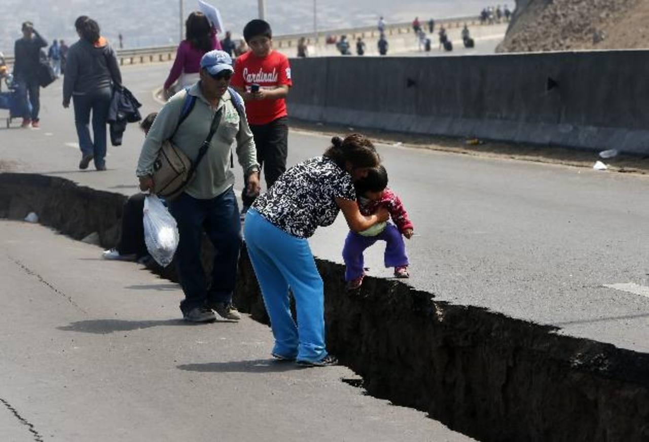 Un grupo de personas camina por una carretera agrietada entre las localidades de Iquique y Alto Hospicio. Foto/ EFE