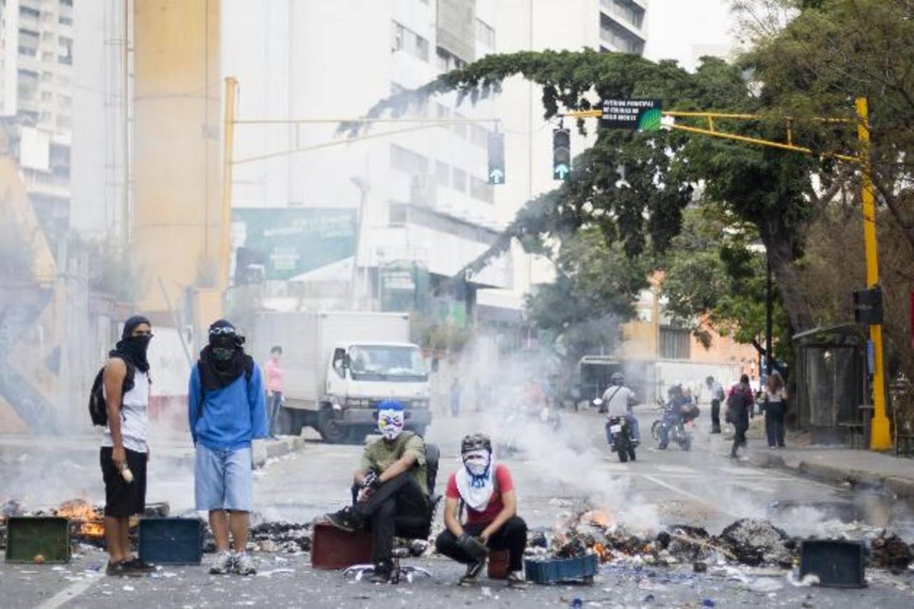 Jóvenes opositores al régimen de Nicolás Maduro bloquean una calle en Bello Monte, Caracas (Venezuela). foto edh /efe