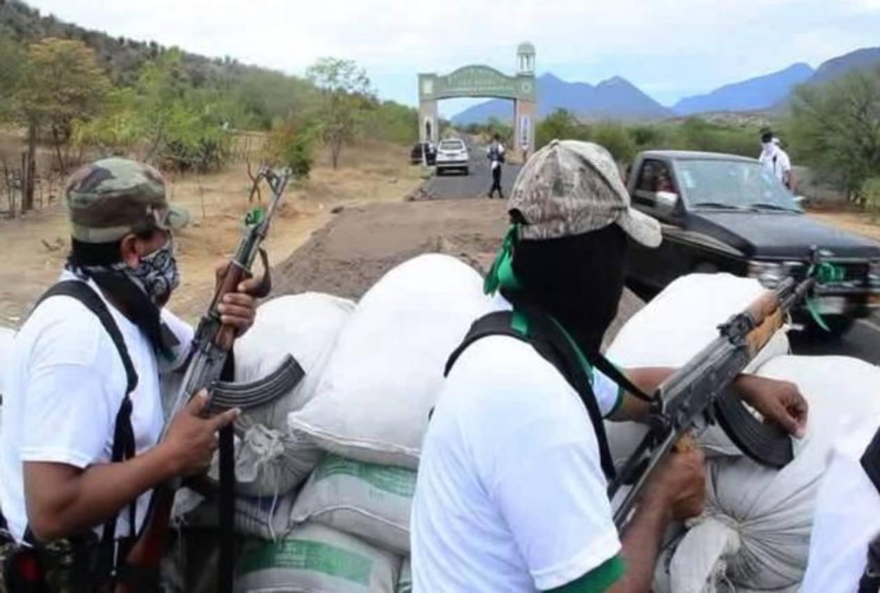 """Fotografía de archivo del 30 de diciembre de 2013 de un grupo de autodefensas vigilando un acceso a la población de Churumuco, Michoacán (México); estos grupos nacieron para combatir al cártel """"Los Templarios"""". foto edh / EFE"""