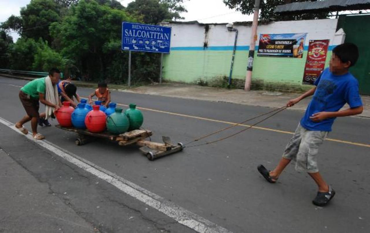 Los niños recorren más de un kilómetro en búsqueda de agua. Para ello tienen que salir a la calle principal. Foto EDH / Cristian Díaz
