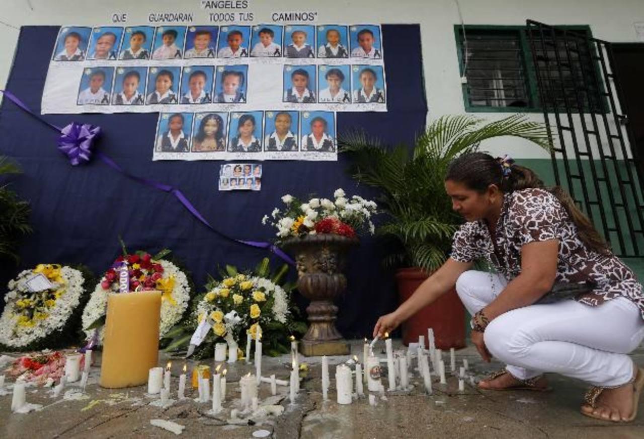 Familiares, alumnos y maestros encienden velas en un altar colocado en la escuela Antonio Nariño en memoria de los niños que murieron en el incendio de un autobús.