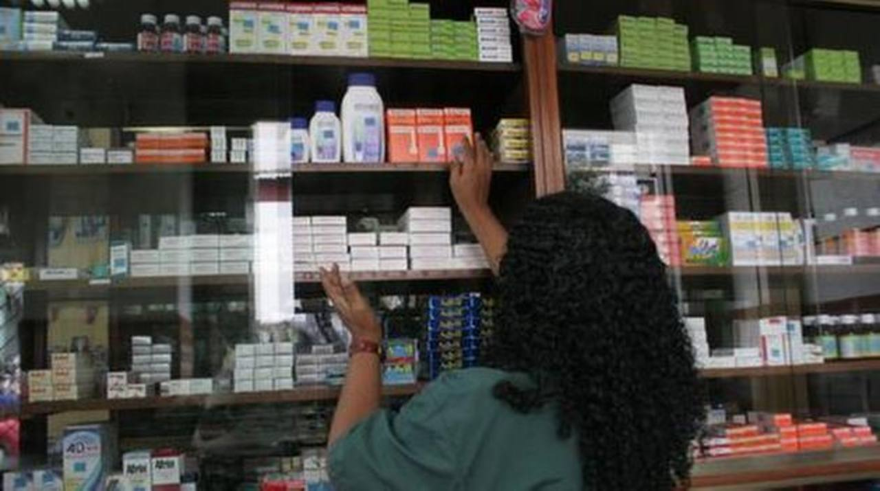 Una empleada de una farmacia en Venezuela busca un medicamento en el estante. El sector reclama su pago atrasado. foto edh