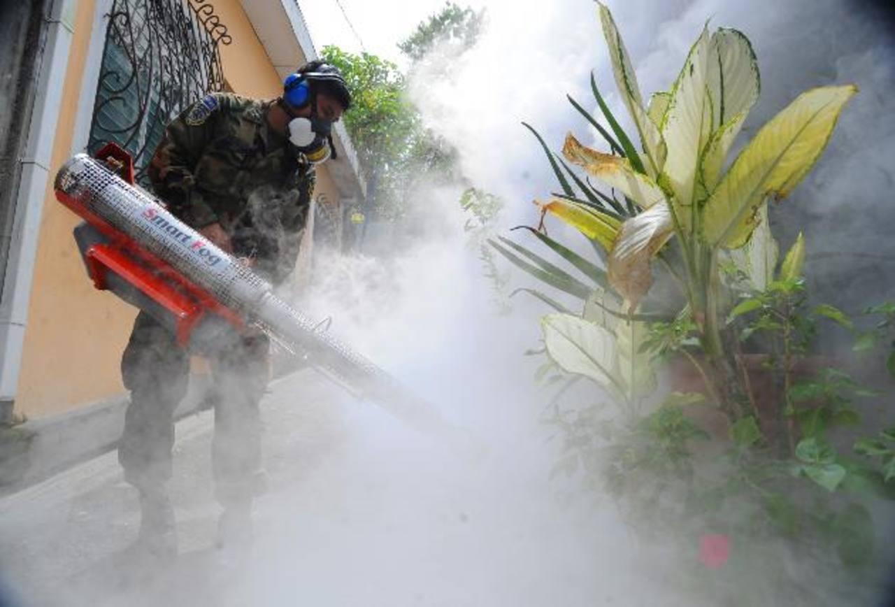 Un elemento de la Fuerza Armada fumiga fuera de una vivienda. La medida sirve para matar al zancudo adultos. Foto EDH