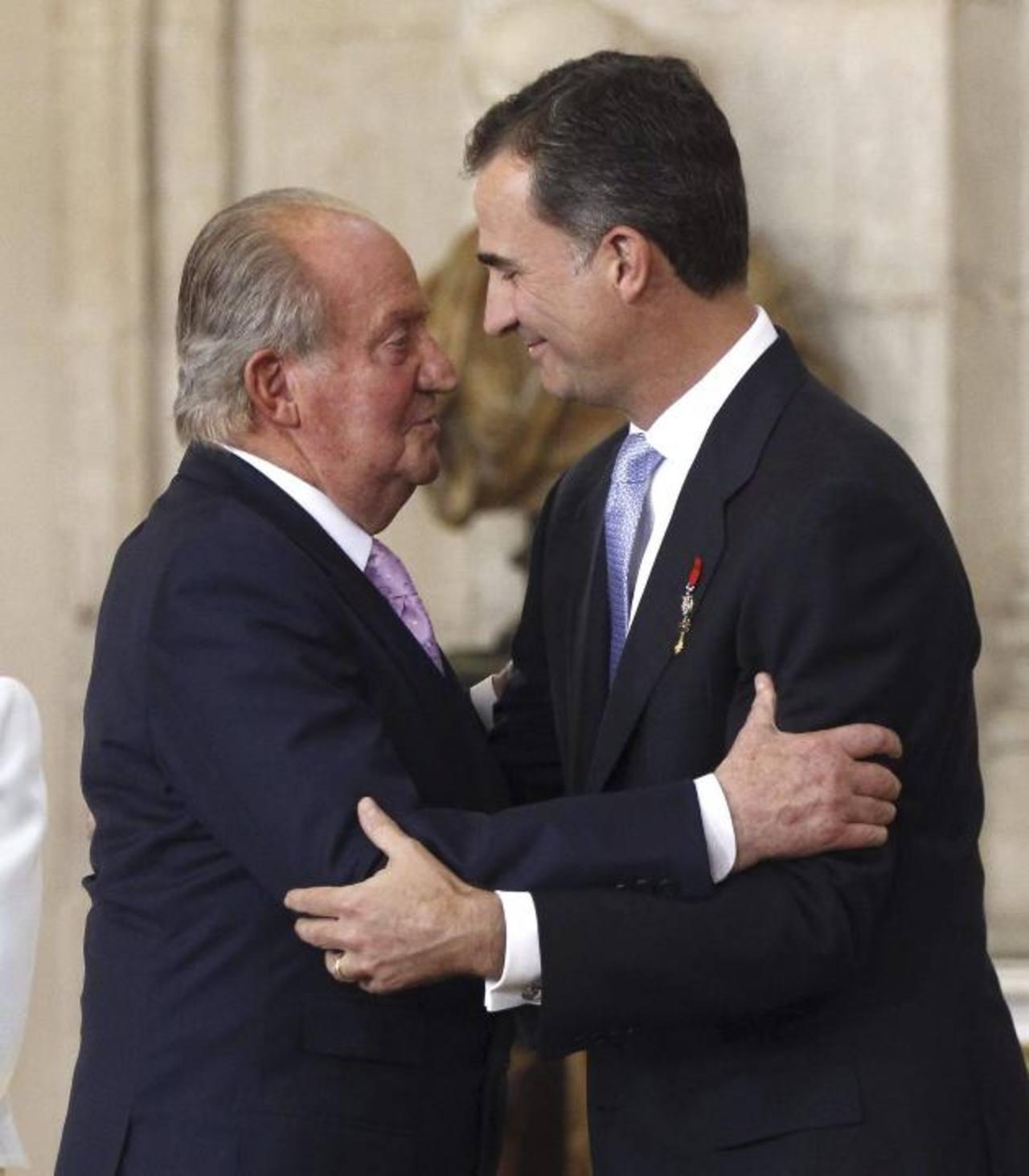 El rey Juan Carlos (izq.) abraza al príncipe de Asturias, Felipe, tras firmar la ley que hace efectiva su abdicación. foto edh /efe