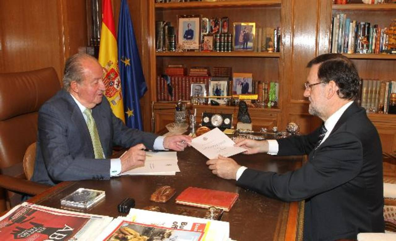 Don Juan Carlos (izq.) firma el documento de su abdicación que ha entregado al presidente del gobierno español, Mariano Rajoy. foto edh / efe