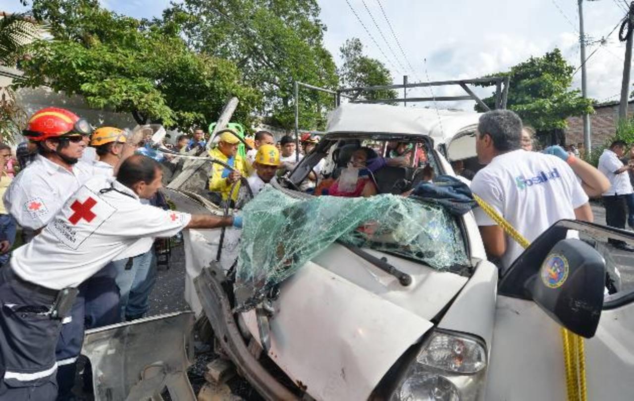 Socorristas trabajan en el rescate de una de las personas atrapadas en la cabina del pick up. Foto EDH / Douglas Urquilla.