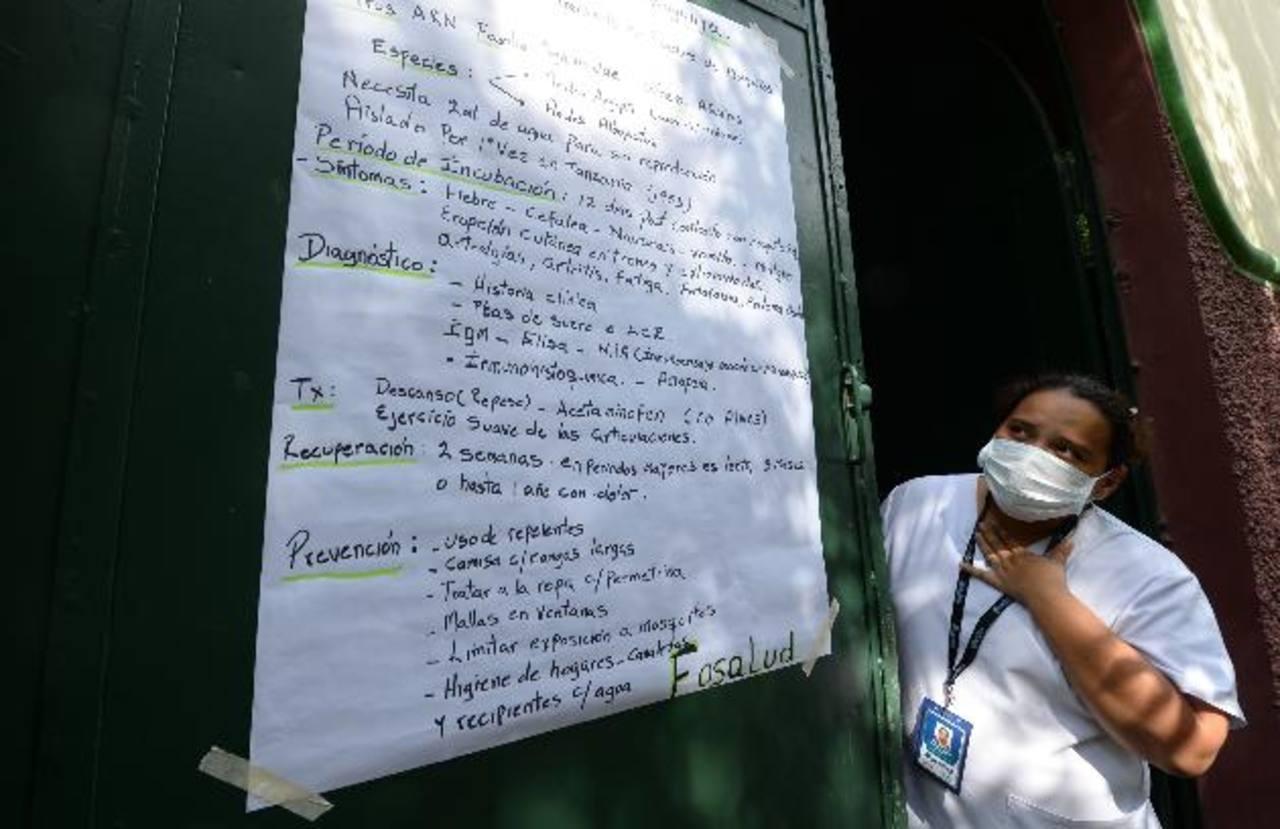 Una enfermera lee sobre la enfermedad chikungunya en la entrada de la casa comunal del cantón Zapote Abajo, en Ayutuxtepeque foto EDH / archivo