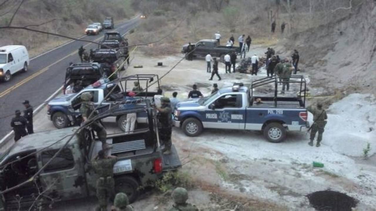 Forenses recaban información donde las autoridades hallaron los cadáveres de 12 personas en una camioneta. foto edh / efe