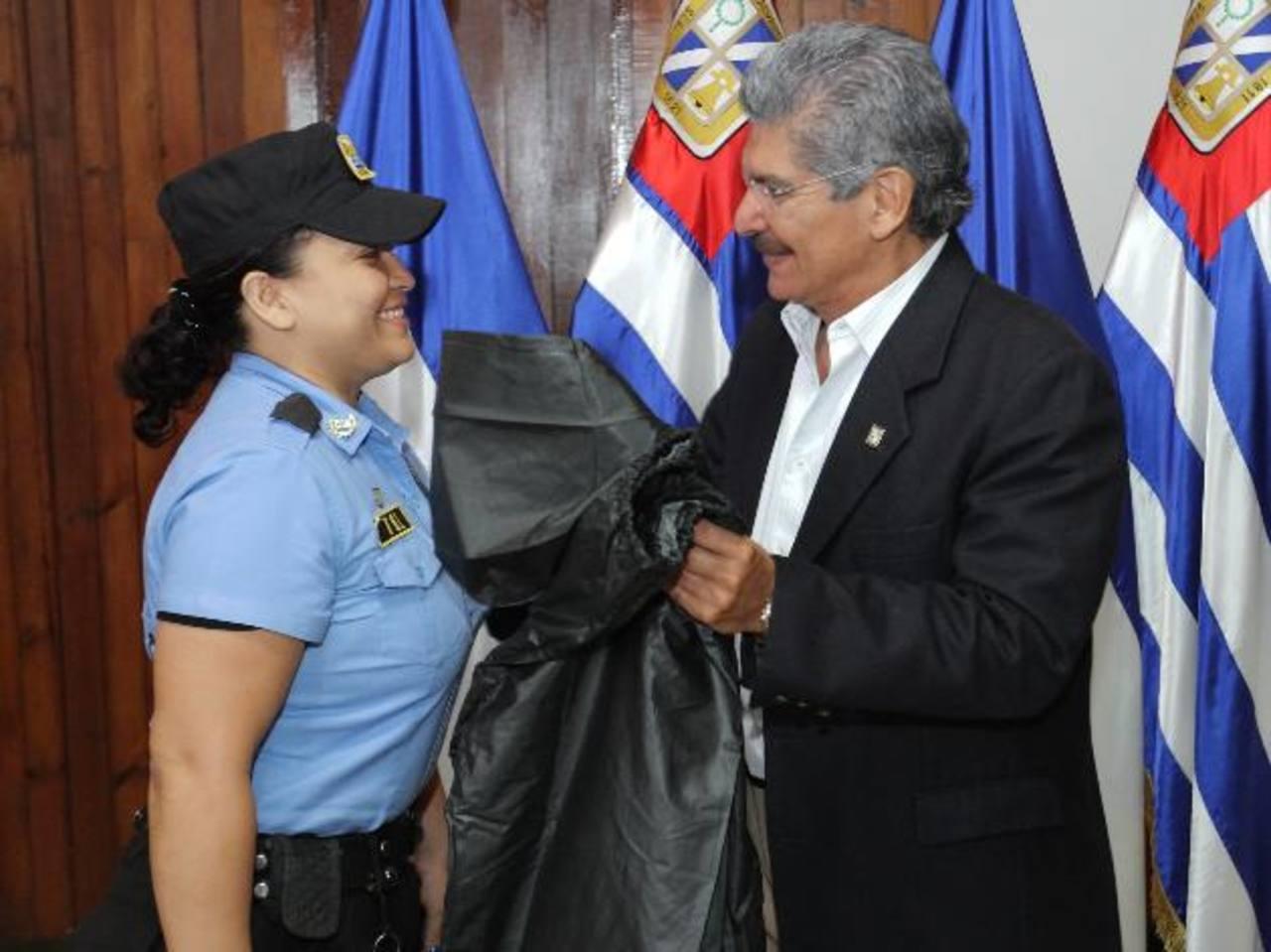 Una agente del CAM recibe del edil Quijano, una capa que forma parte del equipo de trabajo. Foto EDH / Cortesía