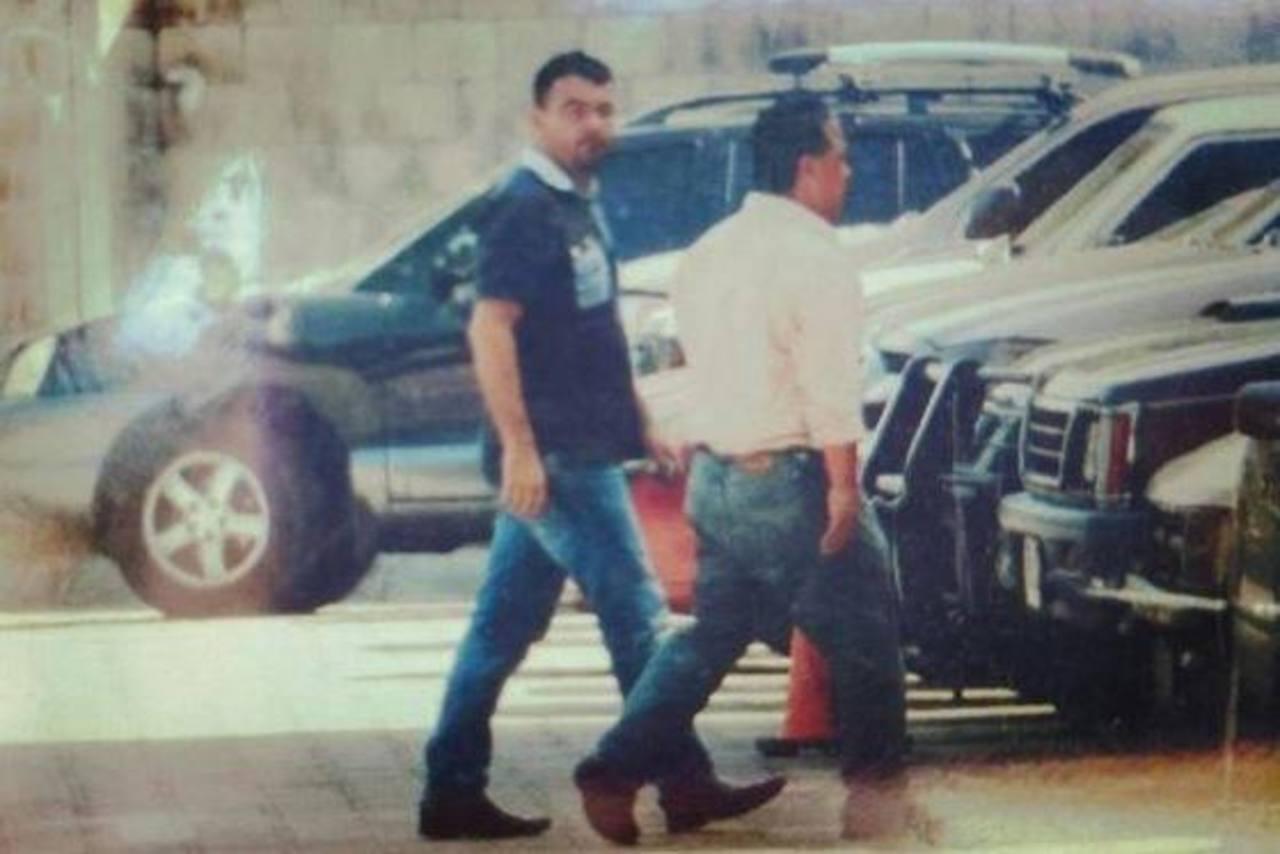 El padre Toño (izquierda) acompañado por un investigador de la policía, en la División de Investifación de la PNC.