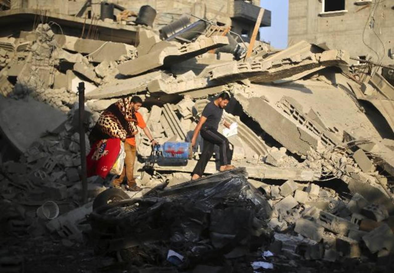 Palestinos rescatan sus pertenencias de una casa que la Policía dijo que fue destruida en un ataque aéreo israelí. foto edh / reuters