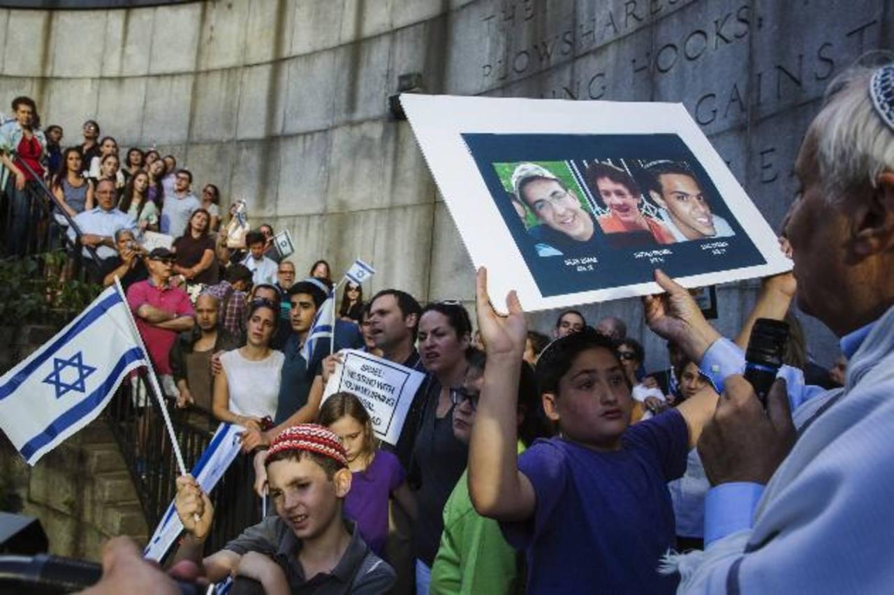 Un niño sostiene una fotografía de los tres jóvenes que fueron secuestrados. foto edh / reuters